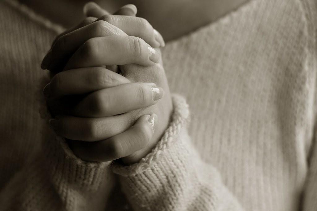 На фото руки девушки, которая молится.