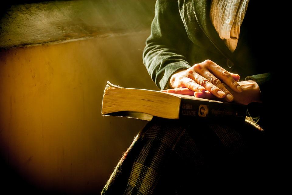 На фото пожилая женщина, читающая Псалтирь.