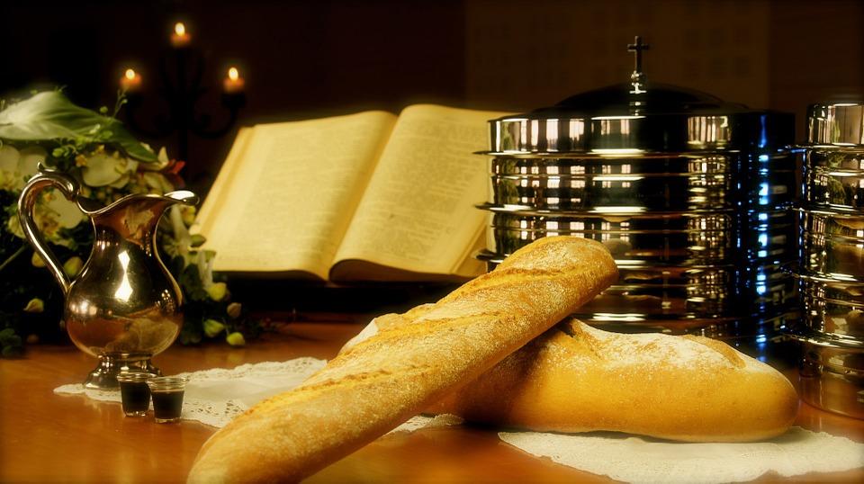 На фото хлеб, вино и церковная книга. Причастие.
