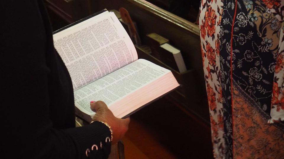 На фото изображена книга Библия, которую в руках держит женщина.