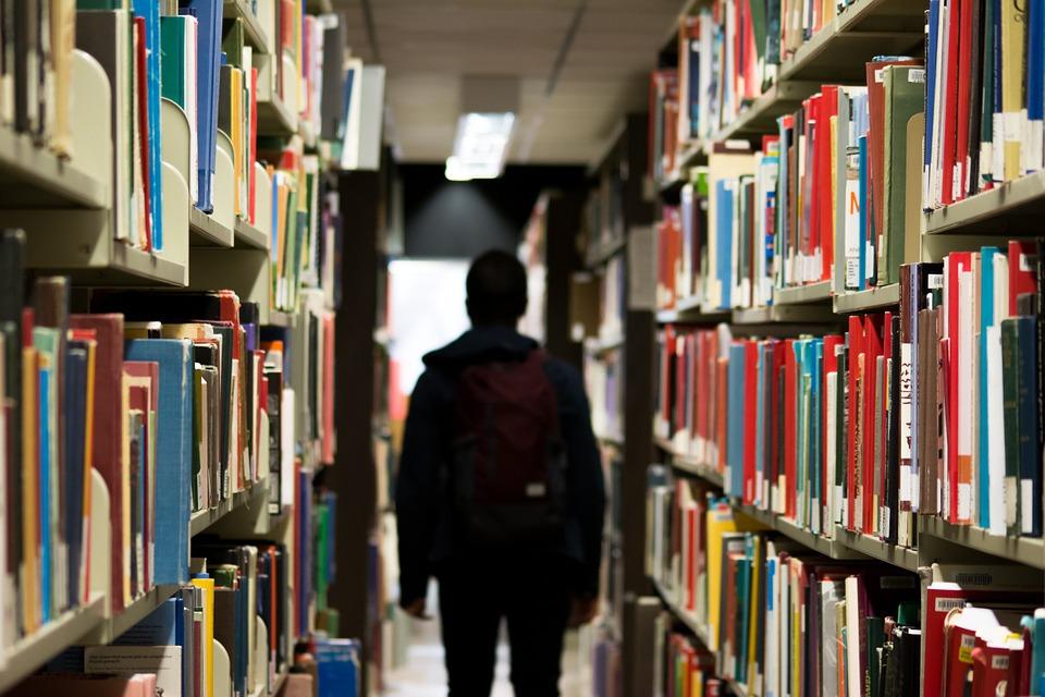 На фот студент в библиотеке среди многих книг.