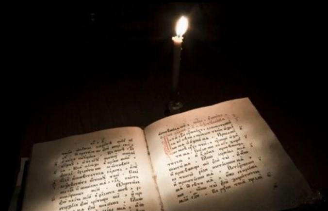На фото книга псалтырь, а рядом горящая свеча.