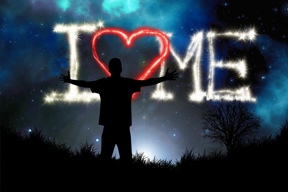 """На фото изображен человек на фоне надписи """"Я люблю себя""""."""