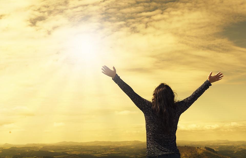 На фото девушка, поднявшая руки вверх, смотрящая на солнце.