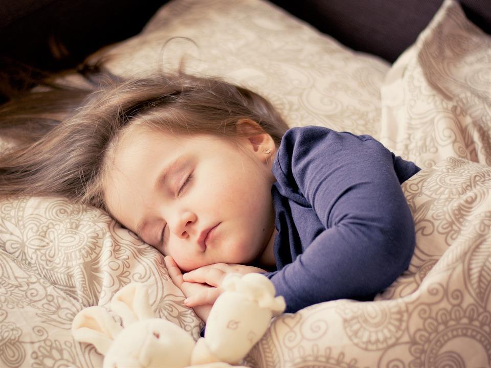 На фото милый ребенок, который спит в кроватке.