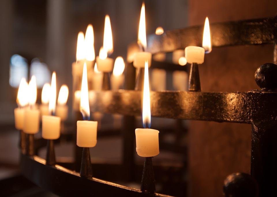 На фото изображены свечи, горящие в храме.
