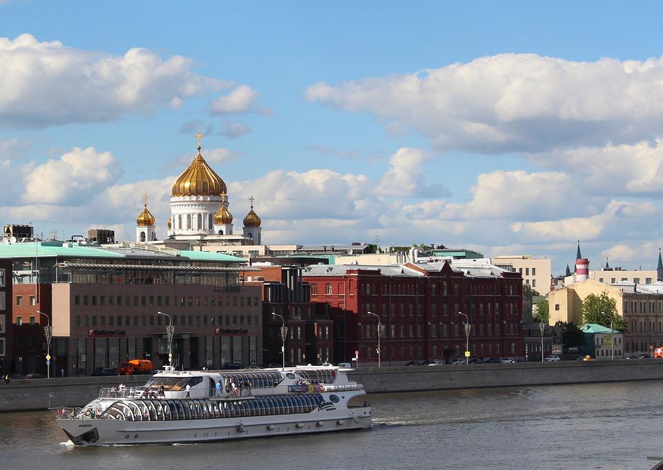 На фото изображена церковь, а на переднем плане река и корабль.