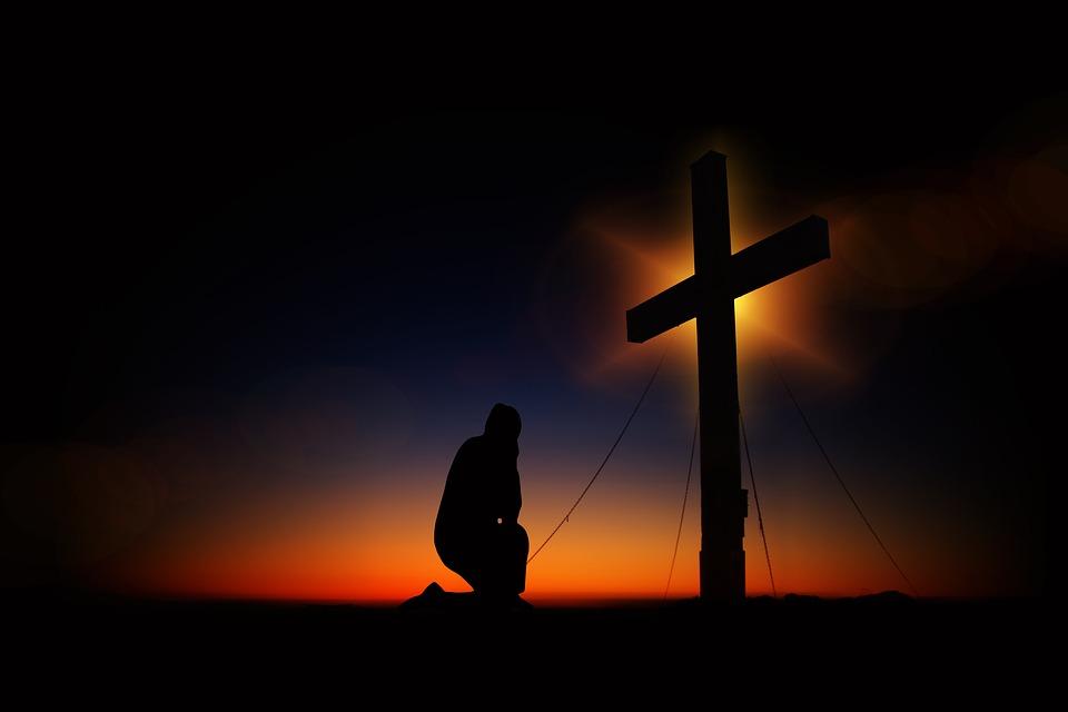 На фото изображен человек, который молиться, опустив голову перед крестом.
