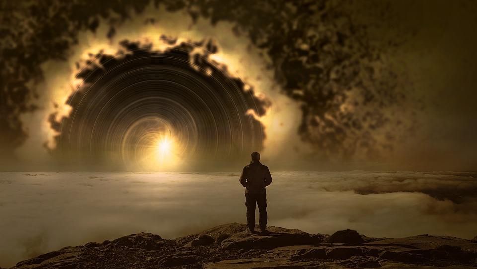 На фото изображен человек, который смотрит вдаль на фантастический пейзаж.