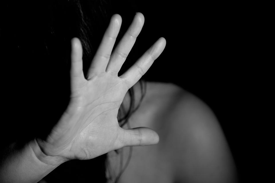 На фото изображена женщина, которая закрыла лицо рукой, словно кого-то боится.