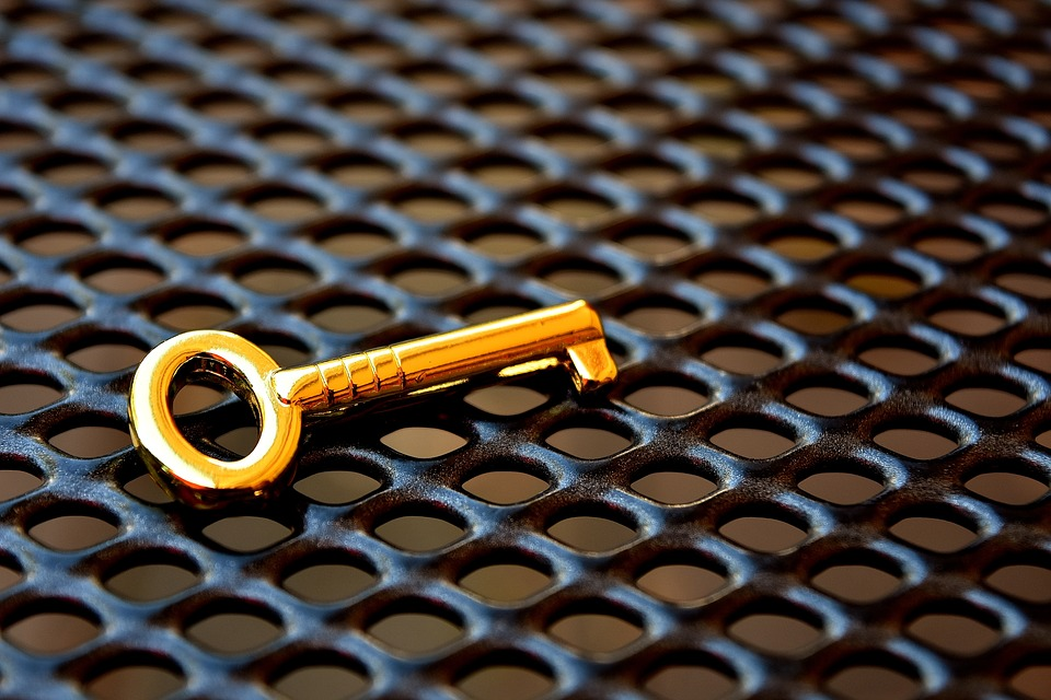 На фото изображен золотой ключ на решетке, как образ взятки.