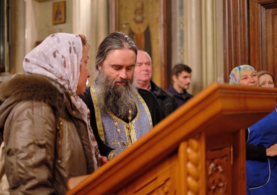 На фото изображен священник в храме и прихожане.