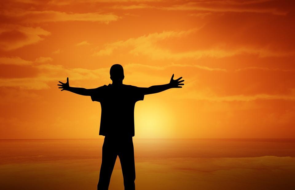 На фото изображен человек, смотрящий на рассвет.