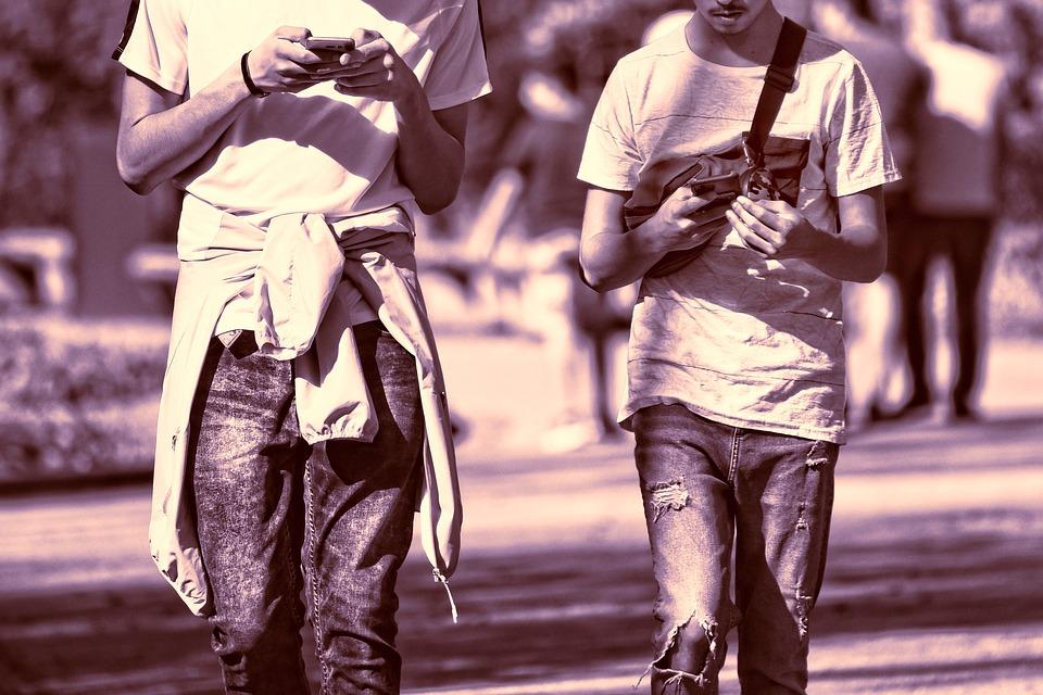На фото два парня, идущих по улице. Они смотрят в мобильные телефоны.