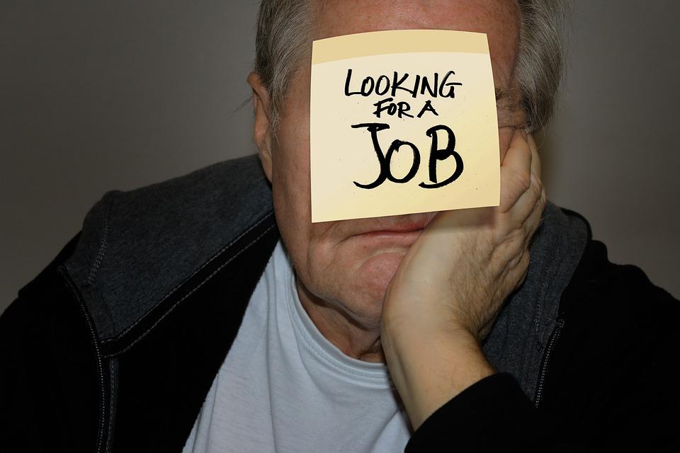 На фото изображение человека с наклейкой на лбу о поиске работы.