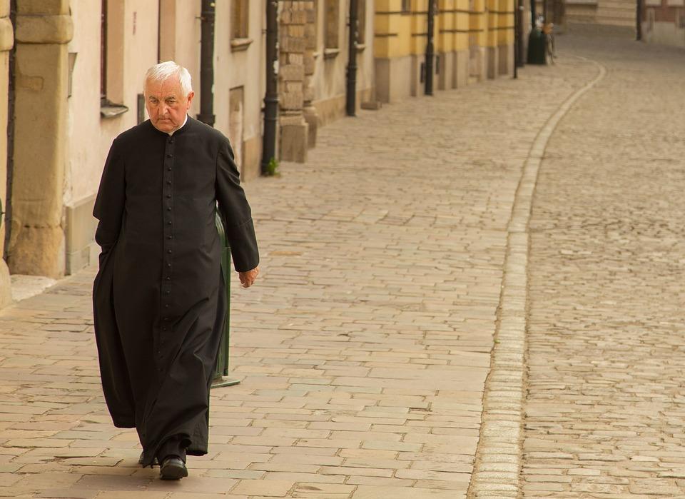 На фото священник, идущий по дороге.