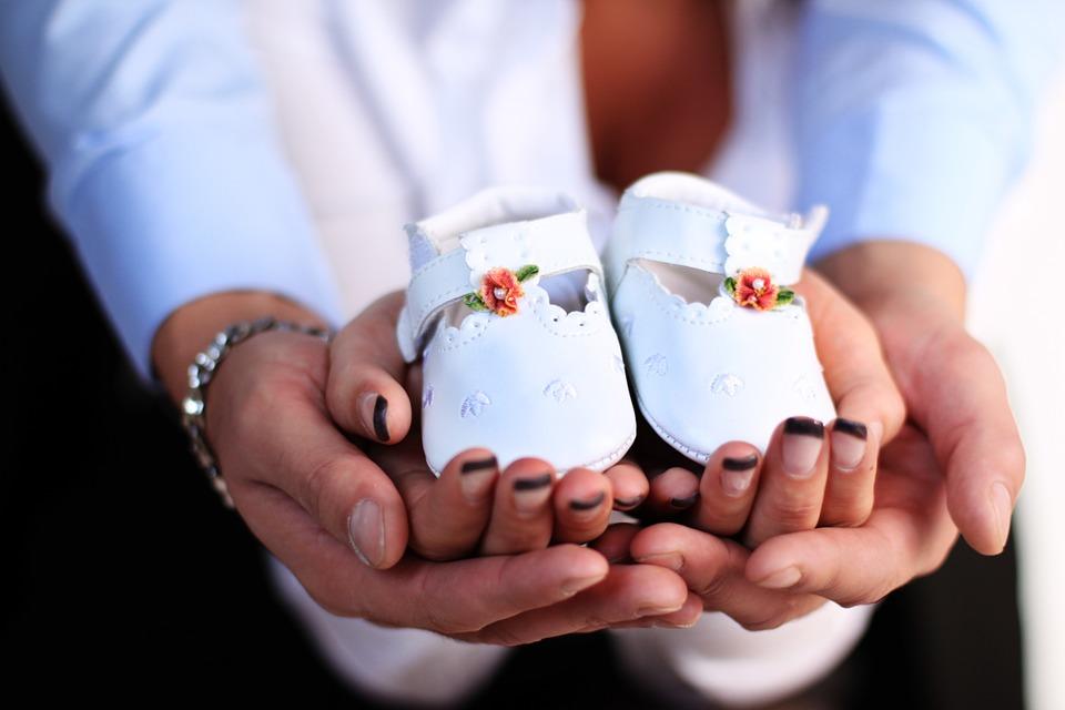На фото изображены руки родителей, держащие детскую обувь.