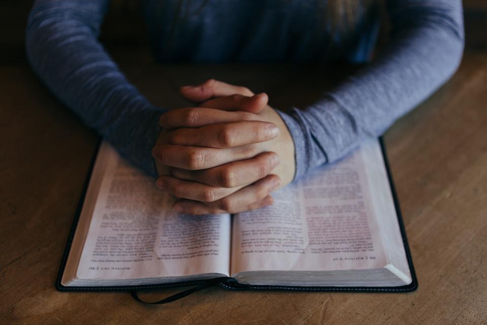На фото Библия и человек, который ее читает, положив руки.