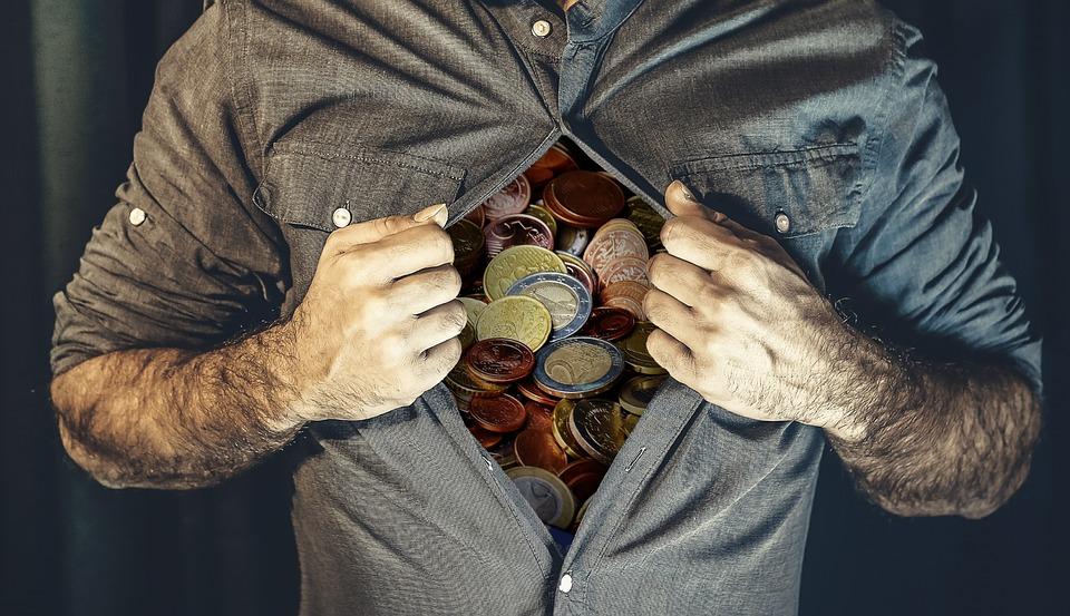 На фото изображен мужчина, разорвавший рубашку, а под ней монеты. Образ материальных ценностей.
