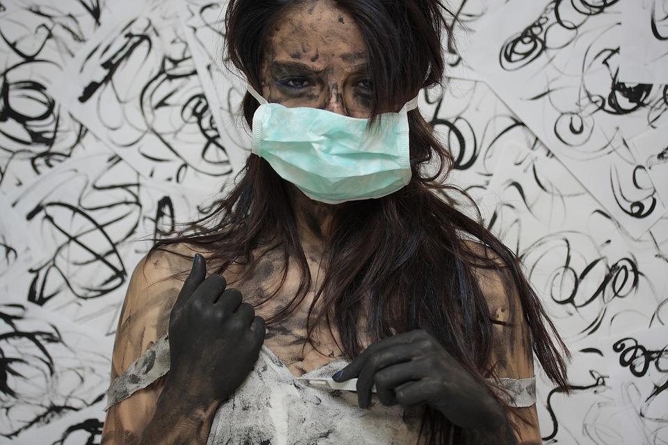 На фото женина в повязке с руками измазанными в чернилах.