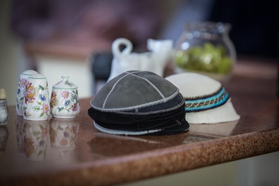 На фото изображены ермолки, символизирующие религию иудаизм.