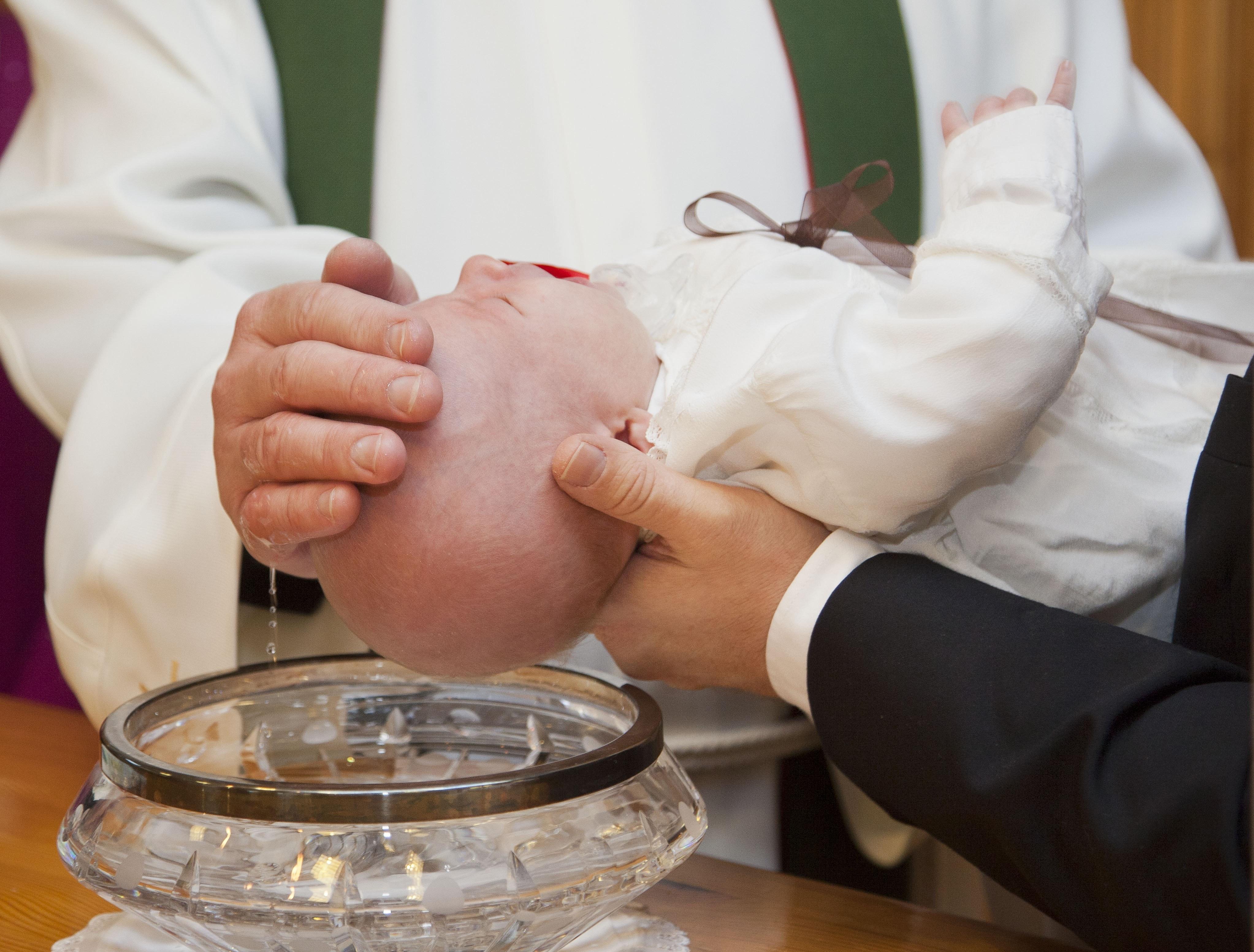На фото изображен обряд крещения ребенка.