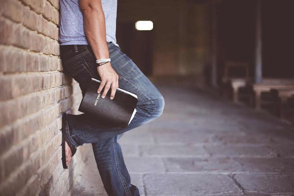 На фото парень с библией в руке.