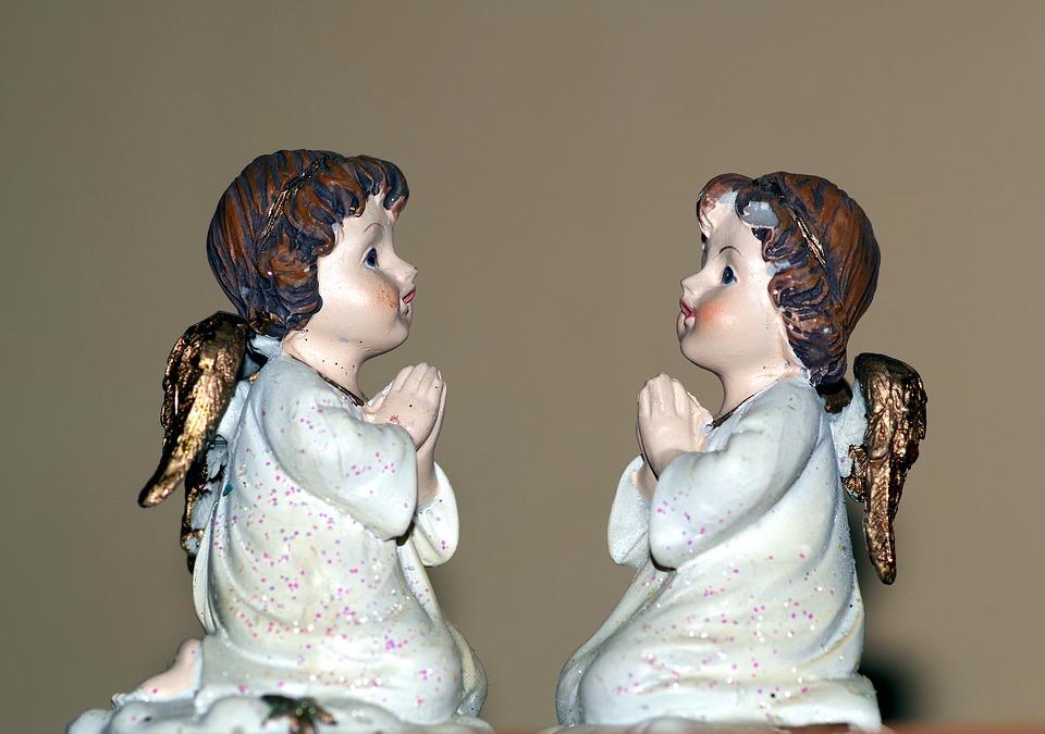 На фото изображены две статуэтки - два маленьких ангелочка, молящихся Господу.