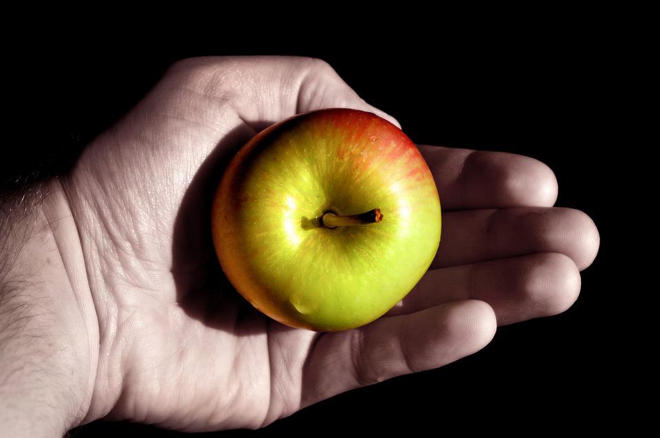 На фото изображена рука держащая яблоко, как символ грехопадения.