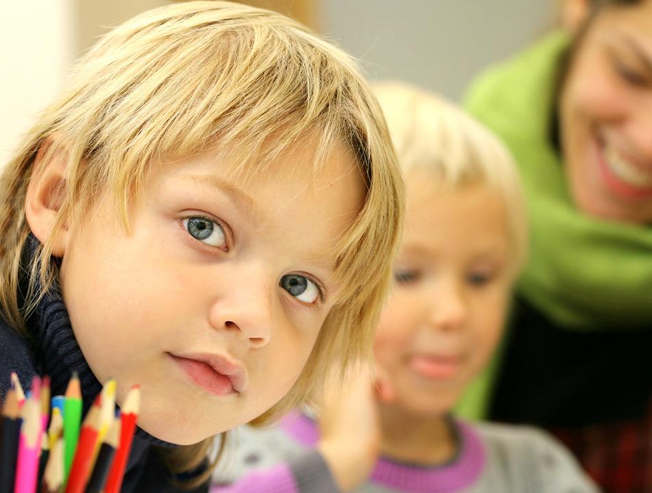 На фото изображен ребенок, который занимается рисованием в школе.