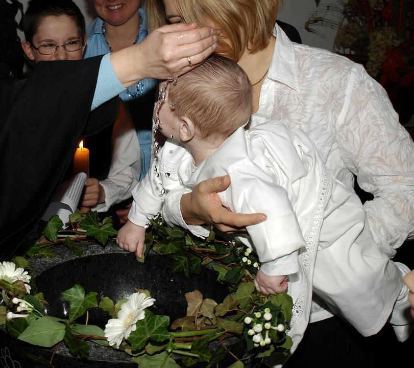 На фото изображено, как крестят ребенка.