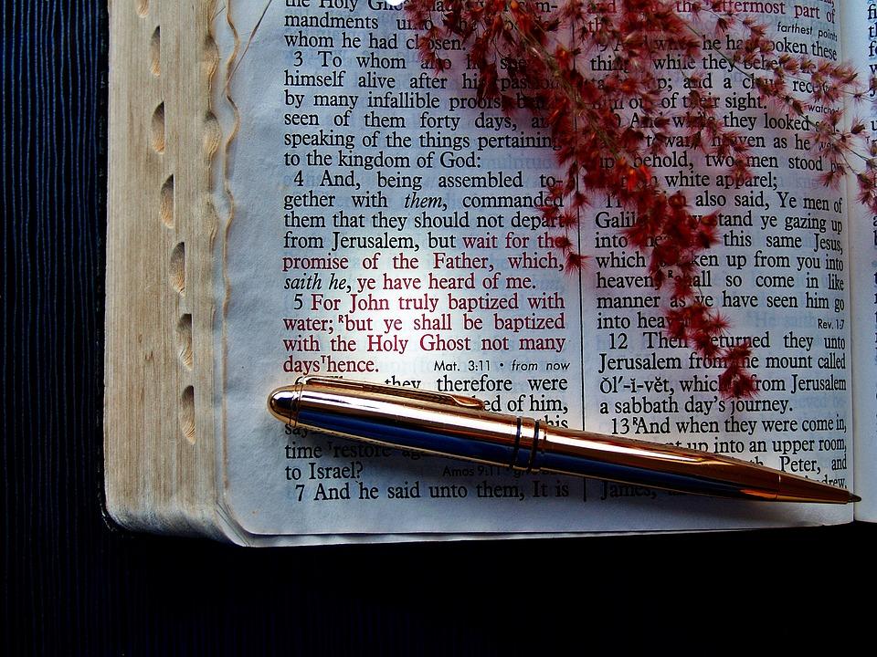 На фото изображена Библия, на которой лежит ручка.