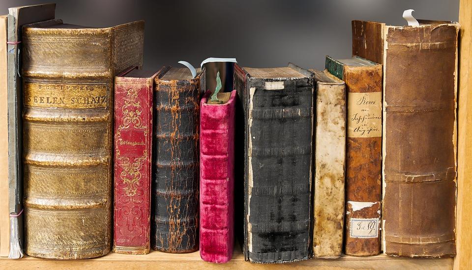 На фото изображены старые книги, лежащие на полке.