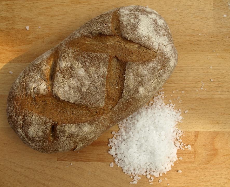 На фото изображены хлеб и соль, лежащие на столе.