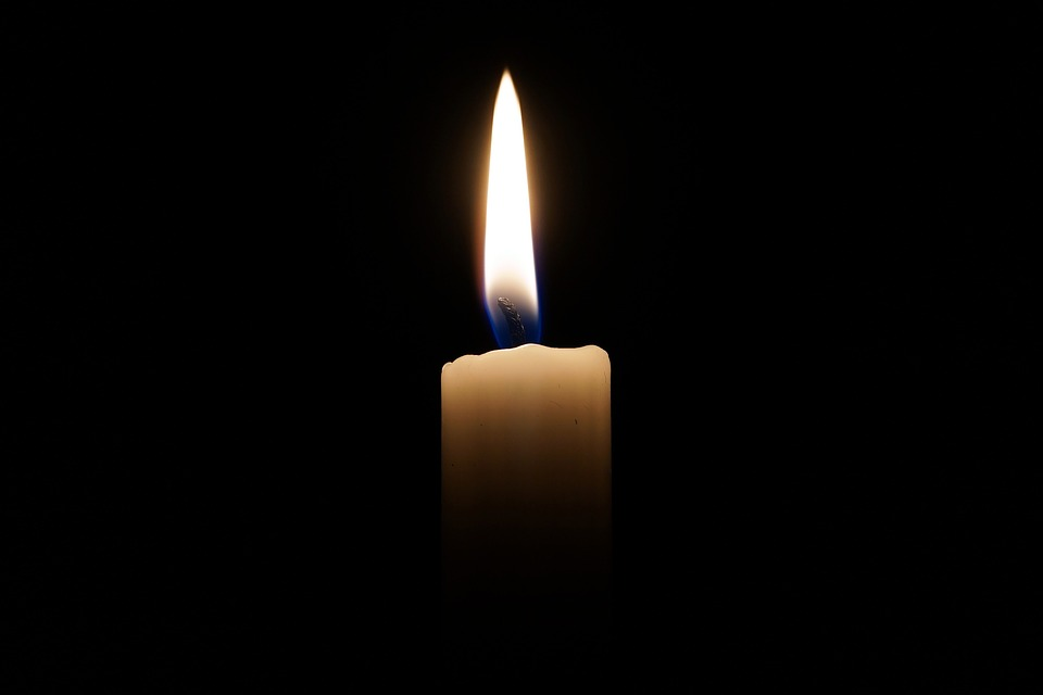 На фото свеча, горящая на черном фоне.