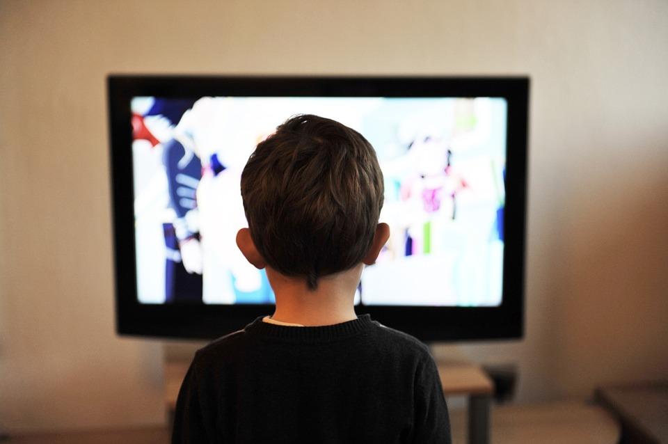 На фото изображен ребенок, смотрящий телевизор.