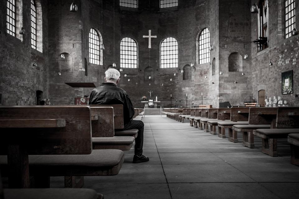 На фото изображен человек, сидящий в храме на лавочке.