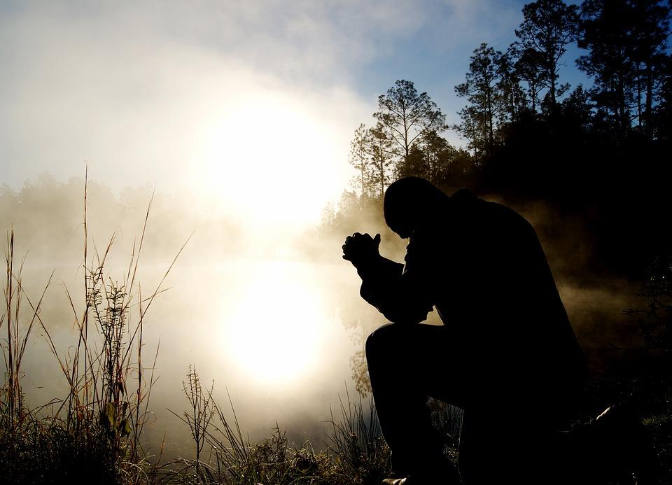 На фото изображен мужчина, который молится, сложив руки. Вокруг него туман, восходит солнце.