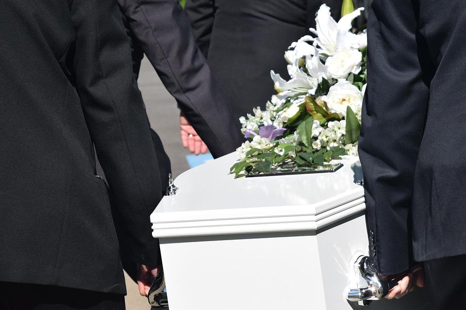На фото изображены люди, несущие гроб.