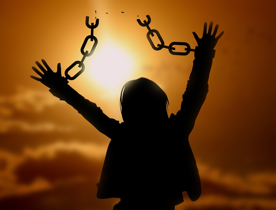 На фото изображена женщина с разорванными цепями на руках.
