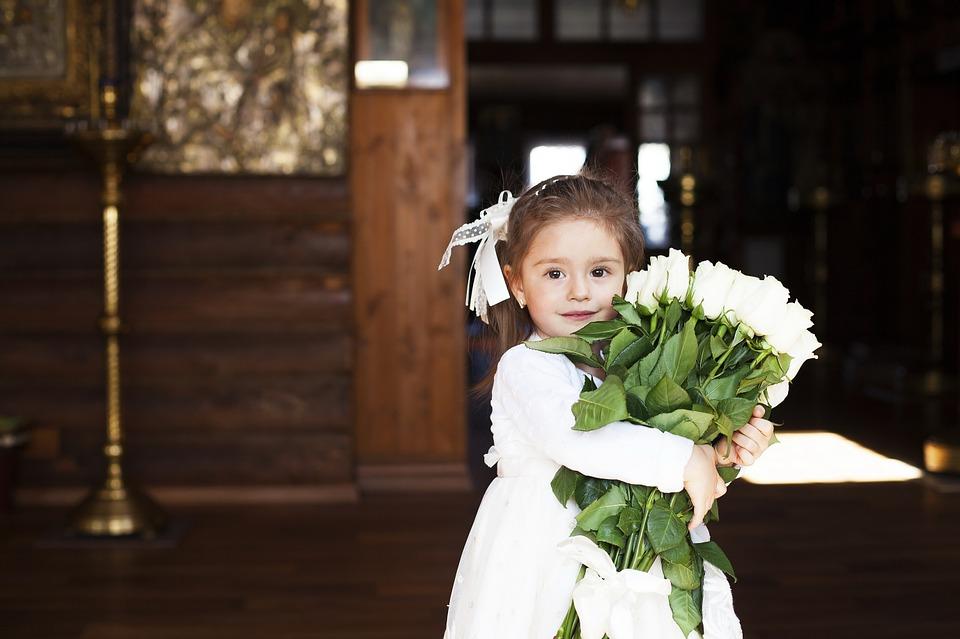 На фото девочка с букетом белых роз, стоящая в храме.