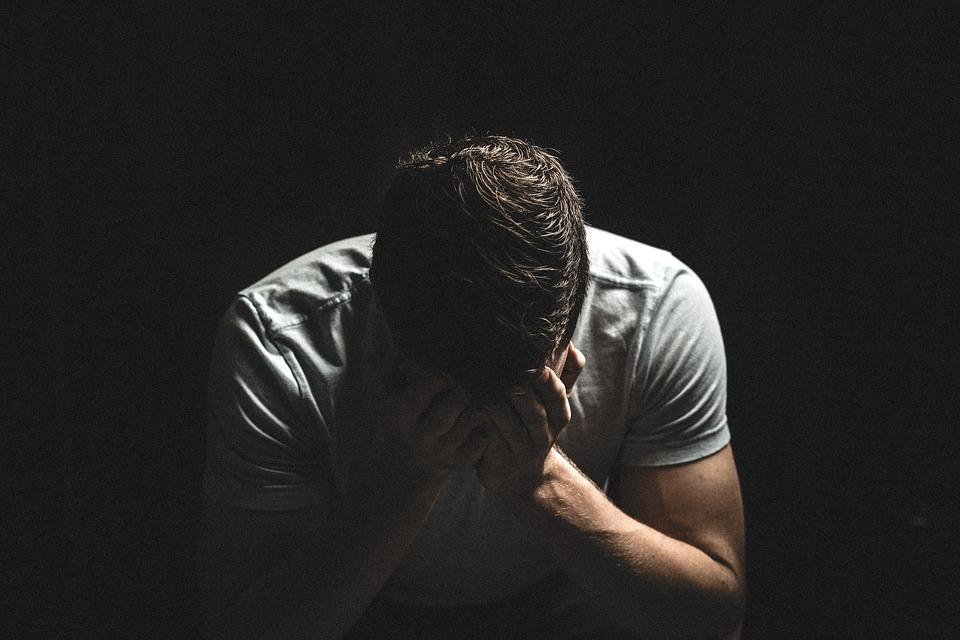 На фото изображен мужчина, который опустил голову и плачет.