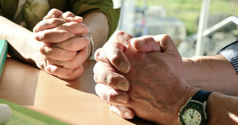 На фото изображены руки людей, которые молятся.