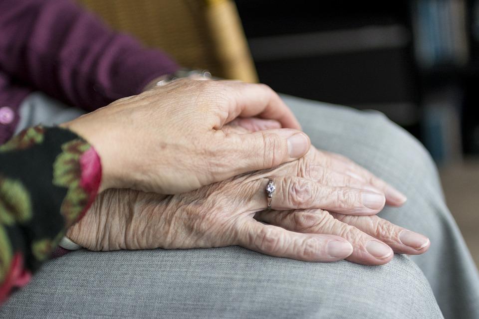 На фото изображены руки пожилой женины, на которые сверху положена рука, как символ поддержки и уважения.