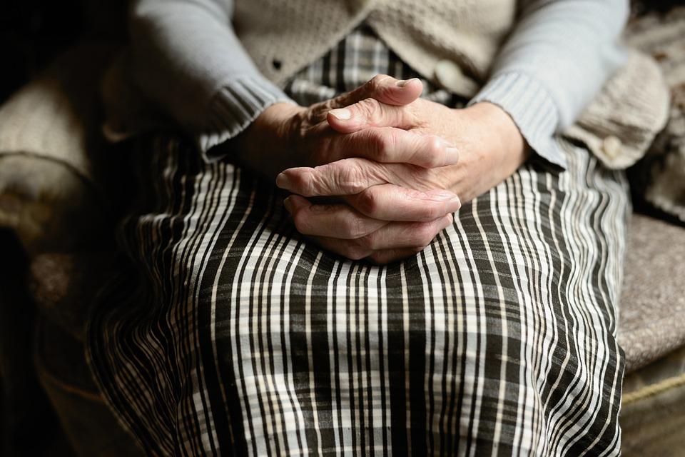 На фото изображены руки пожилой женщины.