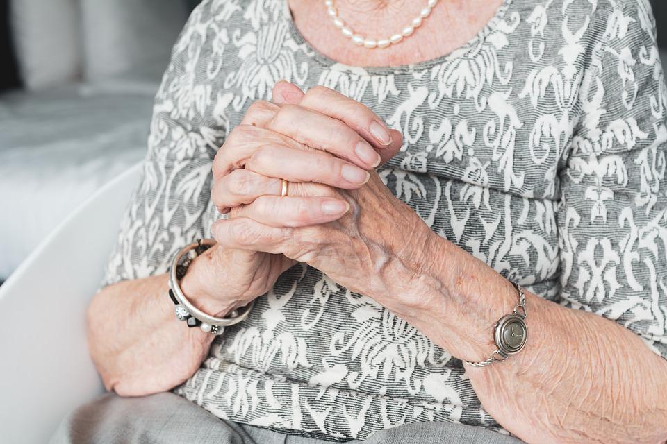 На фото изображены сложенные в молитве руки пожилой женщины