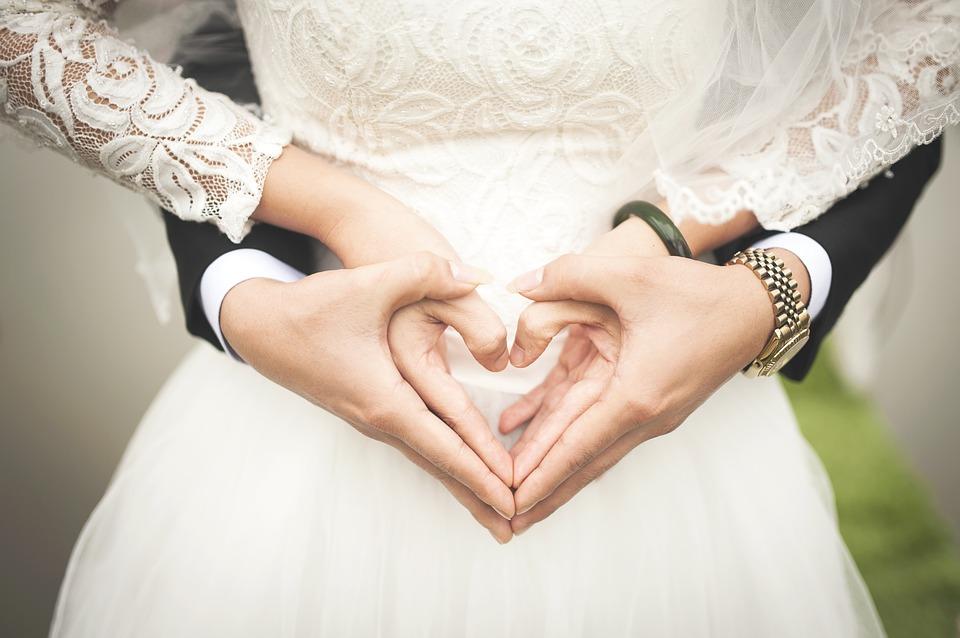 На фото изображены жених и невеста, которые сложили руки в сердечко.