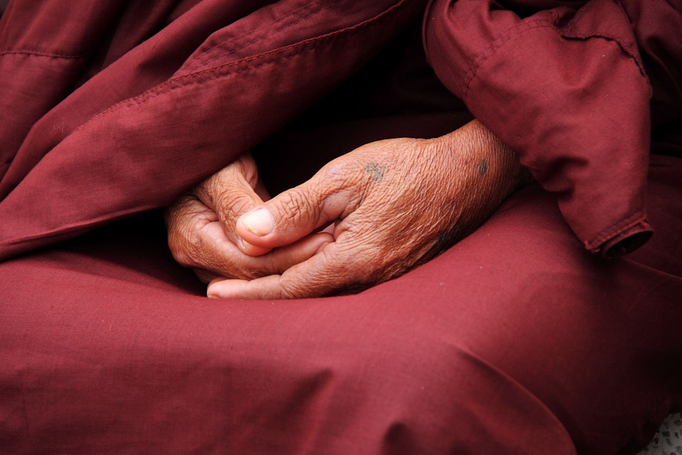 На фото изображены руки старого монаха.