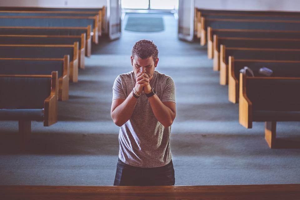 На фото мужчина молится в храме.