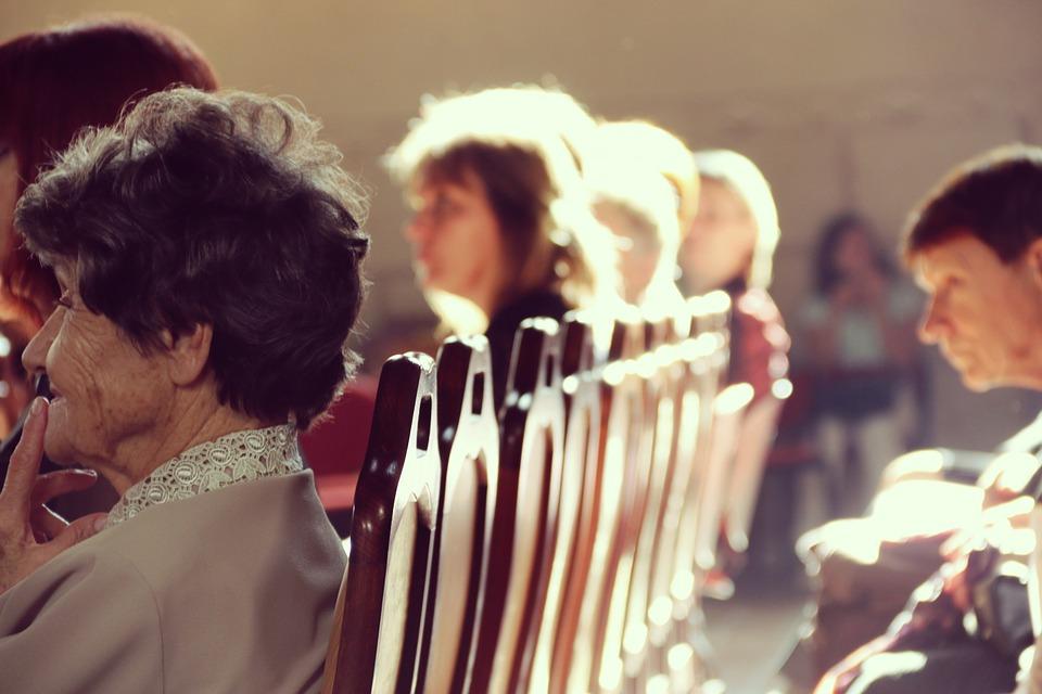 На фото изображены люди, сидящие на стульях в храме.